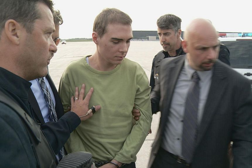 A file photo shows Luke Magnotta (centre) being escorted by police upon arrival from Germany on June 18, 2012 at Mirabel Airport in Mirabel, Quebec, Canada. -- PHOTO: AFP