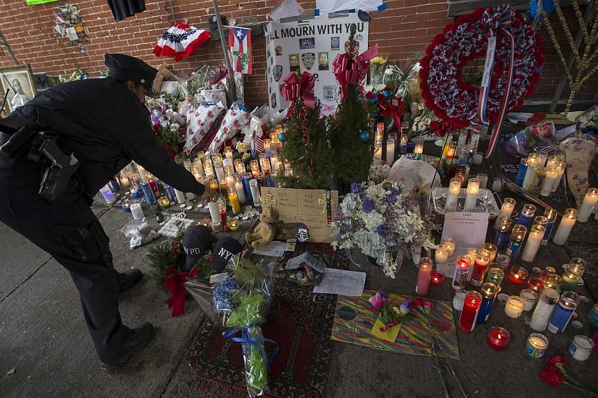 A New York City police officer lights a candle as she visits a makeshift memorial at the site where two police officers were fatally shot in the Brooklyn borough of New York, Dec 23, 2014. Protesters who have rallied for weeks over excessive use