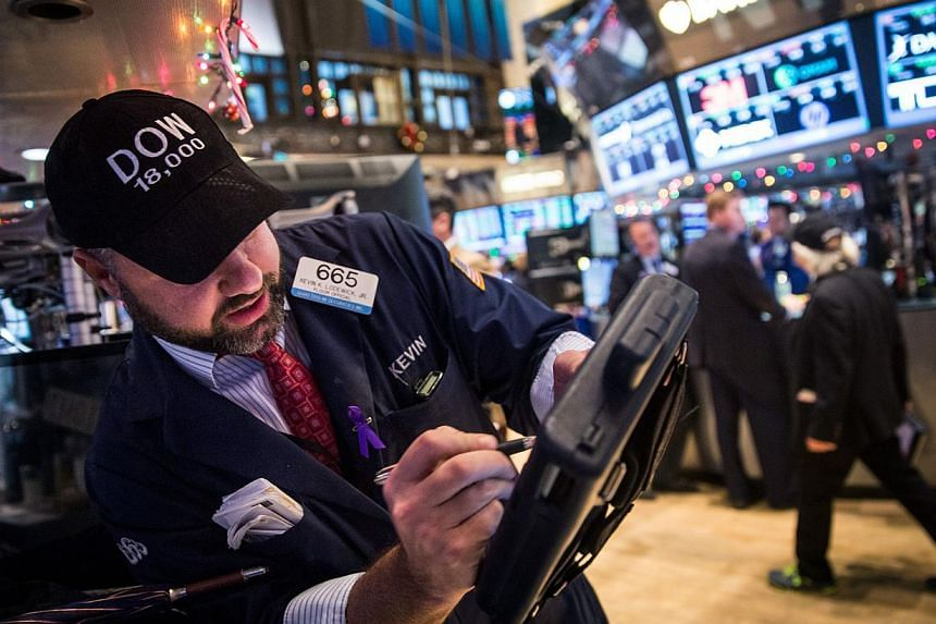 """Traders wear hats that say """"DOW 18,000"""" as they work on the floor of the New York Stock Exchange Tuesday afternoon in New York City. The Dow Jones Industrial Average crossed a landmark by closing above 18,000 points. -- PHOTO: AFP"""