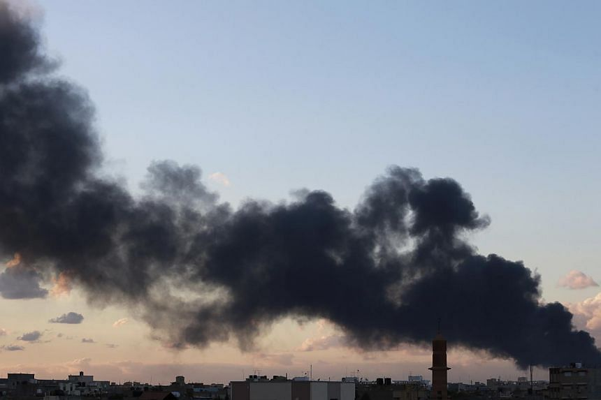 Black smoke billows in the sky above areas where clashes are taking place between pro-government forces, who are backed by the locals, and the Shura Council of Libyan Revolutionaries, an alliance of former anti-Gaddafi rebels, who have joined forces