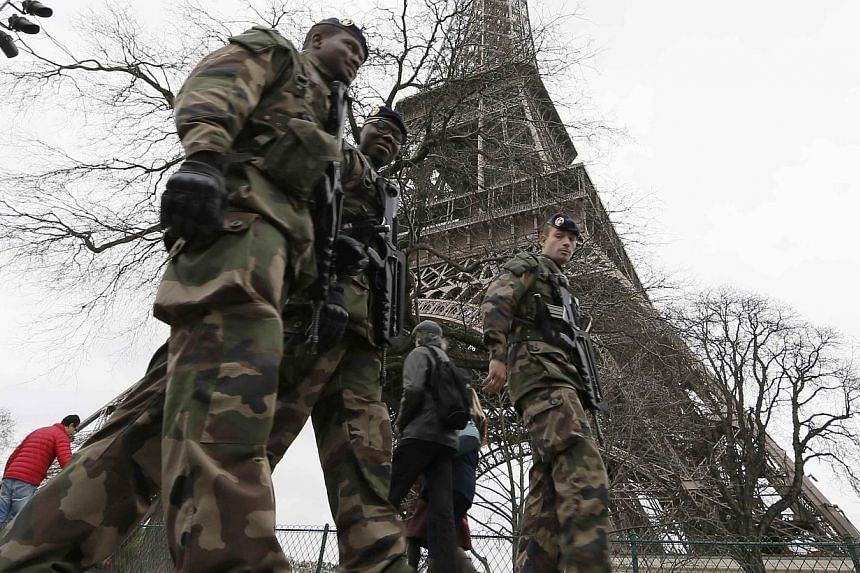 French soldiers patrol near the Eiffel Tower in Paris on Dec 23, 2014. French security forces stepped up protection of public places on Tuesday after three acts of violence in three days left some 30 wounded and reignited fears about France's vulnera