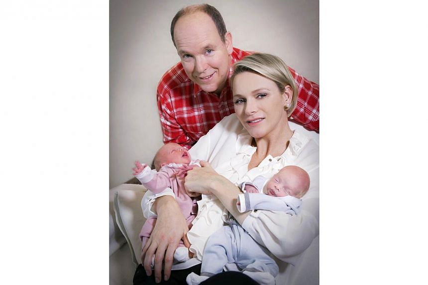 A handout picture released by the Palace of Monaco on Dec 23, 2014 shows Prince Albert II of Monaco and his wife Charlene posing with their twin babies Jacques and Gabriella at the Princess Grace Hospital in Monaco on Dec 22, 2014. -- PHOTO: AFP