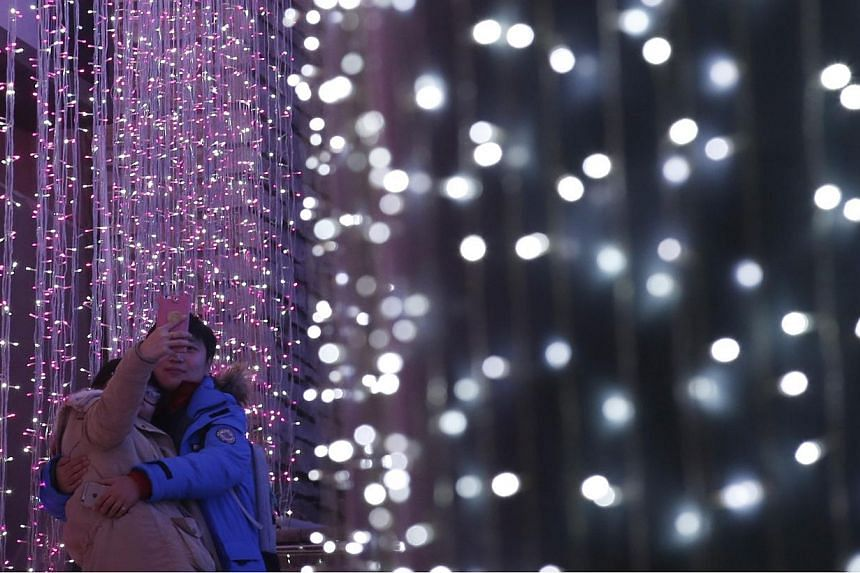 A couple takes a picture in front of a light installation for Christmas celebrations in Beijing on Dec 23, 2014. -- PHOTO: REUTERS
