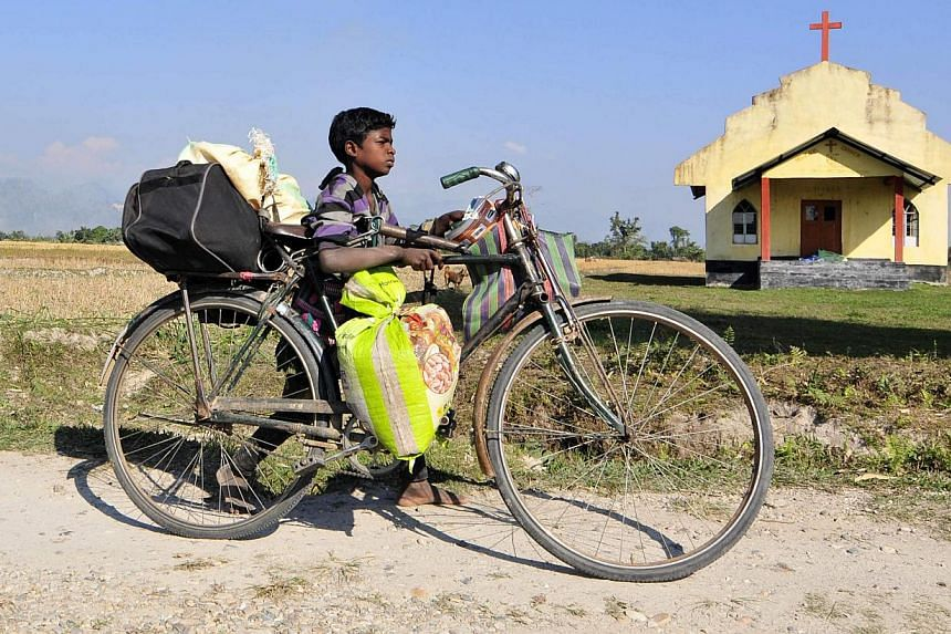 A boy transports his belongings on a bicycle as he moves to a safer place after ethnic clashes in Tenganala village, in Sonitpur district in the northeastern Indian state of Assam on Dec 24, 2014. -- PHOTO: REUTERS