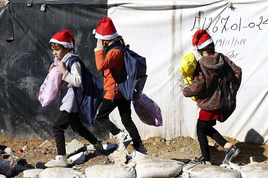 Syrian refugee girls hold their Christmas gifts from SAWA, a non-governmental organisation, in Bar-Elias in the Bekaa valley on Dec 24, 2014. -- PHOTO: REUTERS