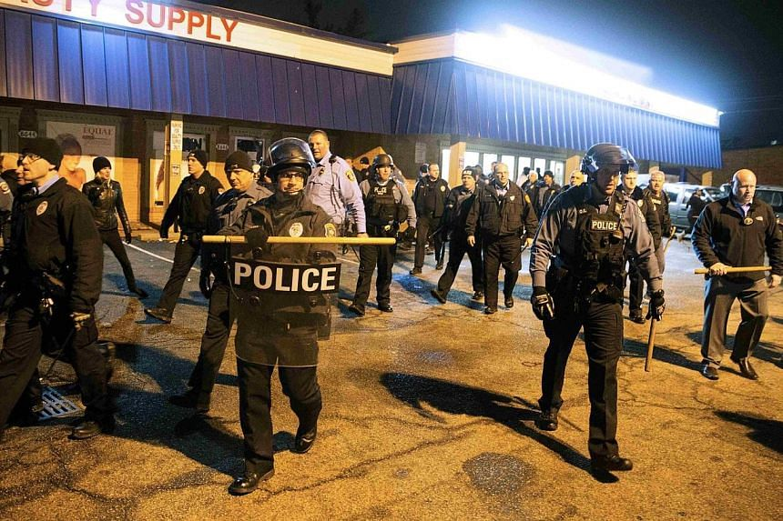 Police clear a parking lot of protesters after a man was fatally shot by a policeman, in Berkeley, Missouri, on Dec 24, 2014.Protests flared into early Thursday in the St. Louis suburb where a white policeman fatally shot a black man who brandi