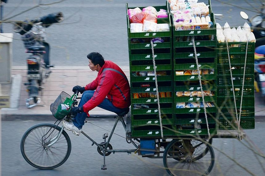 A vendor rides a loaded tricycle along a street in Beijing on Dec 8, 2014.China's economy is creating more than 13 million new jobs this year, the Xinhua news agency cited the labour ministry as saying on Thursday, outstripping the official tar