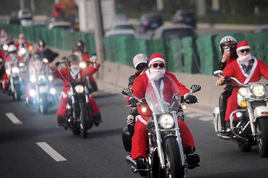 Owners of Harley-Davidson motorcycles wearing Santa Claus costumes ride along a street to give presents to elders at a nursing home during a promotional event celebrating Christmas in Guangzhou. A Chinese city has banned schools from holding Christma