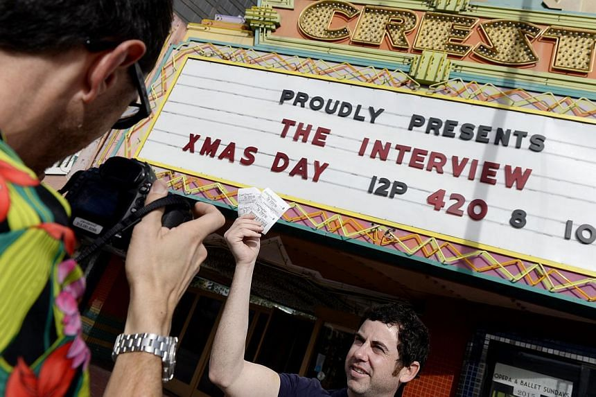 Tickets for the film The Interview is seen held up by theatre manager Donald Melancon for the media at Crest Theater in Los Angeles, California Dec 24, 2014. -- PHOTO:REUTERS
