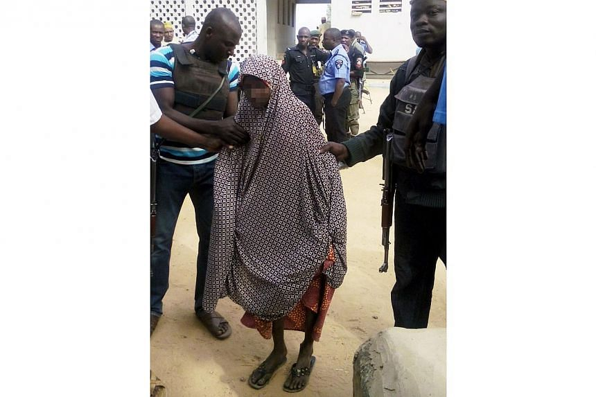 Zahra'u Babangida (centre), a 14-year-old Nigerian girl arrested with explosives strapped to her body in Kano on Dec 10 following a double suicide bombing in a market that killed 10 people, is assisted by police at the Kano state police headquarters