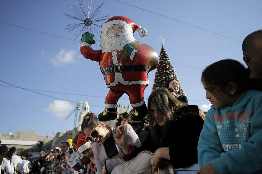 People watch Christmas celebrations outside the Church of the Nativity, the site revered by Christians as Jesus' birthplace, in the West Bank town of Bethlehem Dec 24, 2014. -- PHOTO: REUTERS
