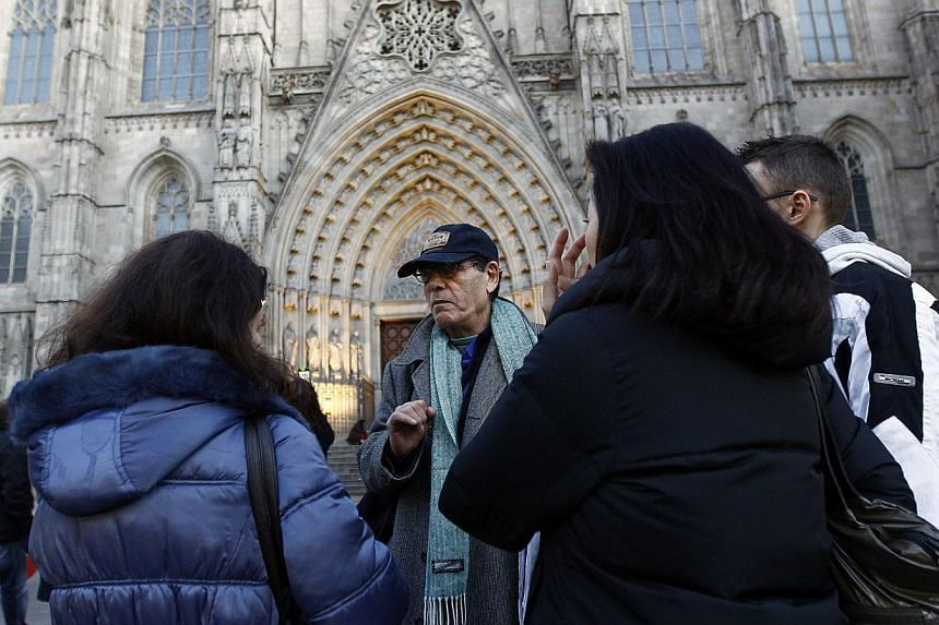 Ramon Holgado (center) conducts a tour for Barcelona Hidden City Tours, a startup company which offers homeless people a job as tour guides in Barcelona. -- PHOTO: AFP