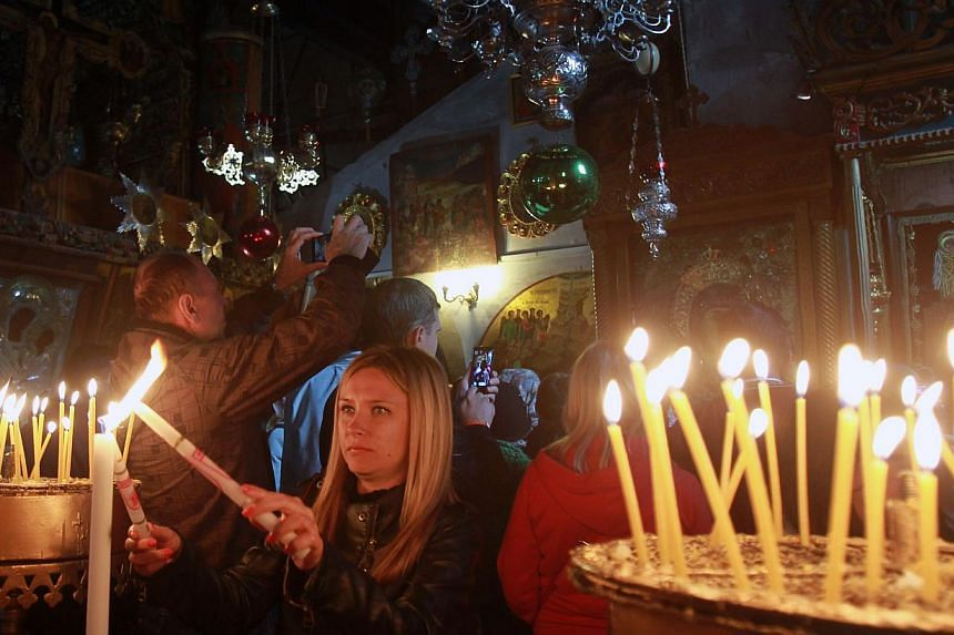 Christian worshippers light candles inside the Church of the Nativity, believed to be the birthplace of Jesus Christ, in the West Bank biblical town of Bethlehem, on Dec 23, 2014. -- PHOTO: AFP