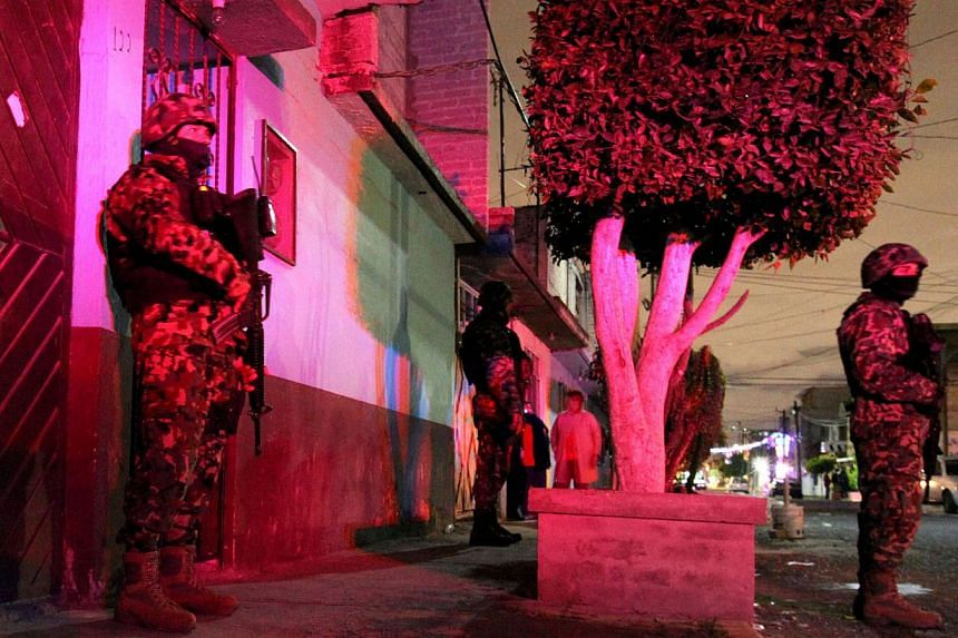 Members of the Mexican Army remain outside the house where a family - including six children - was killed, in the municipality of Ecatepec, state of Mexico, on Dec 24, 2014. A Mexican soldier is suspected of strangling his six children and beating hi