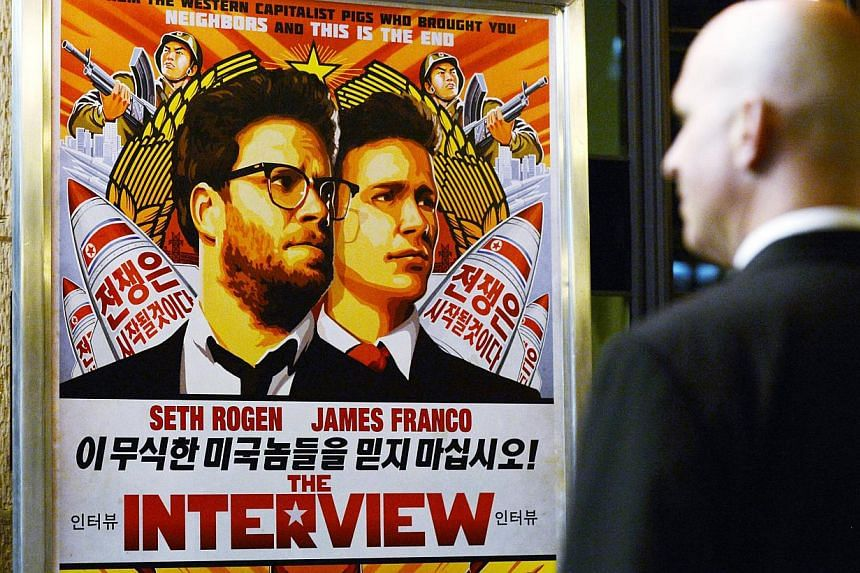 A security guard checks out a poster for the movie The Interview at a cinema in Los Angeles, California, in this Dec 11, 2014 file photo.Sony Pictures said it will make the comedy movie, The Interview, available for rental and purchase online o