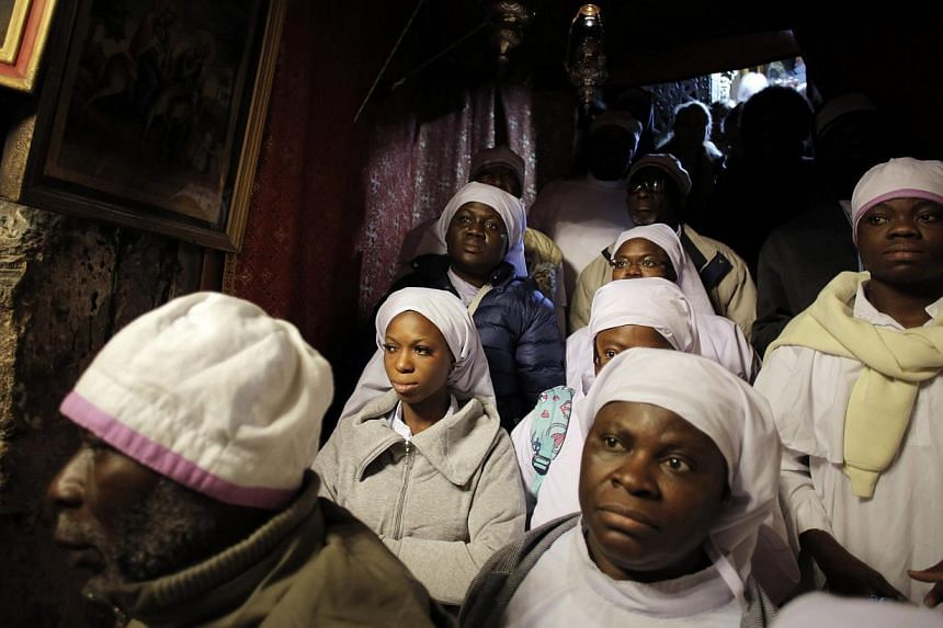Nigerian pilgrims pray inside the Grotto, where Christians believe the Virgin Mary gave birth to Jesus, during Christmas celebrations at the Church of the Nativity in the West Bank town of Bethlehem Dec 24, 2014. -- PHOTO: REUTERS