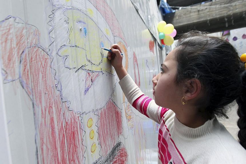 A displaced Iraqi Christian girl who fled from Islamic State militants in Mosul, draws a picture of Santa Claus at a mall still under construction, used as a refugee camp in Arbil Dec 24, 2014. -- PHOTO: REUTERS