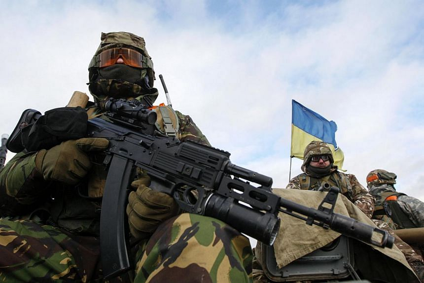 """Ukrainian servicemen sit atop an armoured personnel carrier at a military base in the town of Kramatorsk, eastern Ukraine, Dec 24, 2014. Ukranian and rebel envoys concluded """"difficult"""" marathon talks on Wednesday without agreeing the date of a new ro"""