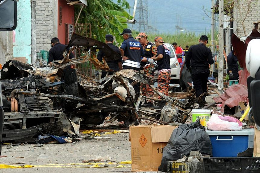 Police and Fire & Rescue Department Forensic Team carrying out investigations at the blast scene at Taman Ria Mesra II in Gurun, Kedah. -- PHOTO: THE STAR