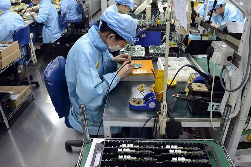 Workers at Add-Plus, an electronics manufacturing company that makes printed circuit boards. -- ST PHOTO: DESMOND FOO