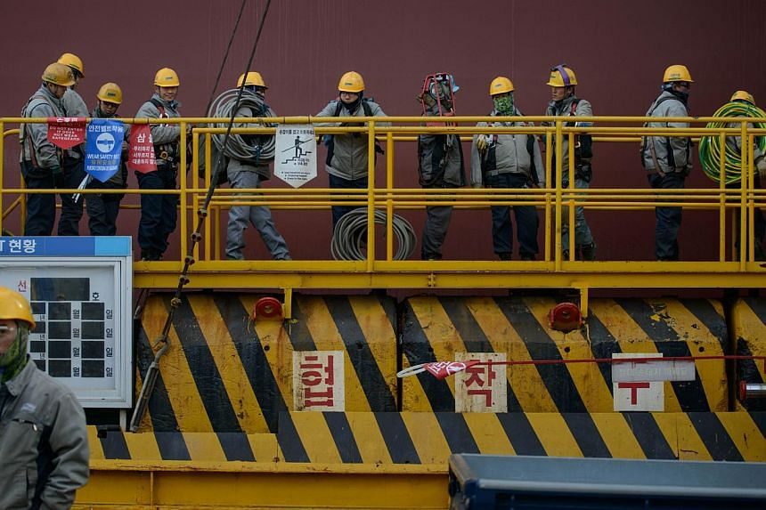 """Workers queueing to enter an under-construction container ship at the Daewoo DSME shipyard in Okpo, South Korea. South Korea has finalised details on a plan to tax """"excessive"""" cash reserves held by companies. -- PHOTO: AFP"""
