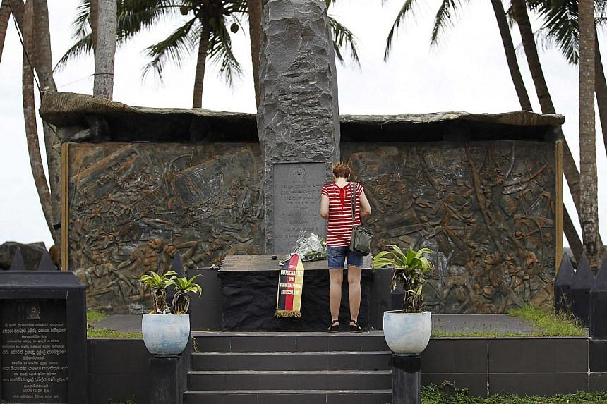 A tourist standing in front of the Tsunami memorial in Pereliya, Sri Lanka, on Dec 20, 2014. More than 250,000 people died in the tsunami on Dec 26, 2004. Indonesia bore the brunt, but Sri Lanka was the next worst-affected country with a death toll o