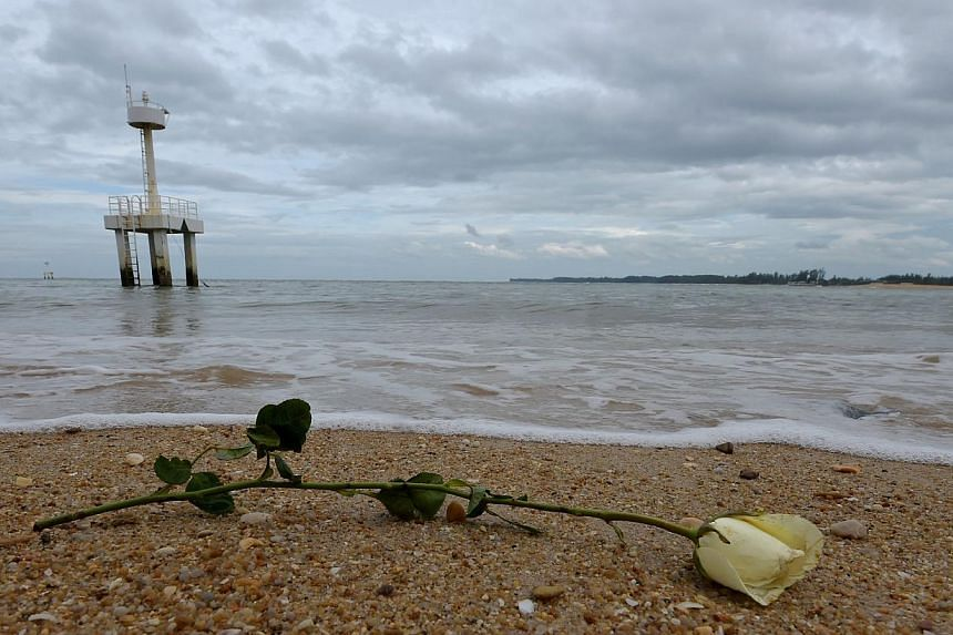 A rose sits on the beach near the Ban Nam Khem tsunami memorial park wall as the tenth anniversary of the 2004 tsunami is remembered in Phang-nga province on Dec 26, 2014. -- PHOTO: AFP