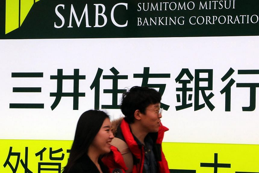 Pedestrians passing by a branch of the Sumitomo Mitsui bank in Tokyo on Dec 25, 2014. Sumitomo Mitsui Financial Group will buy the Japanese retail business of US banking giant Citigroup. -- PHOTO: AFP