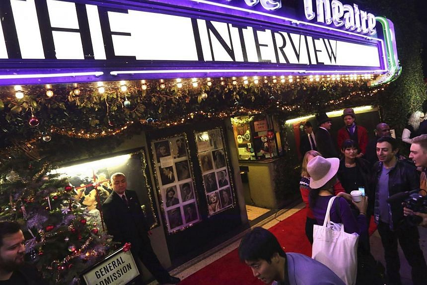 Dennis Lavalle holding a ticket and a poster of the film The Interview before the Christmas Day screening of The Interview in the Van Nuys section of Los Angeles, California, on Dec 25, 2014. -- PHOTO: REUTERS