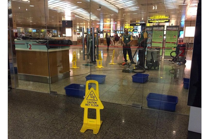 Workers mopping up the wet floor at Changi Airport Terminal Two. -- ST PHOTO: ONG WEE JIN