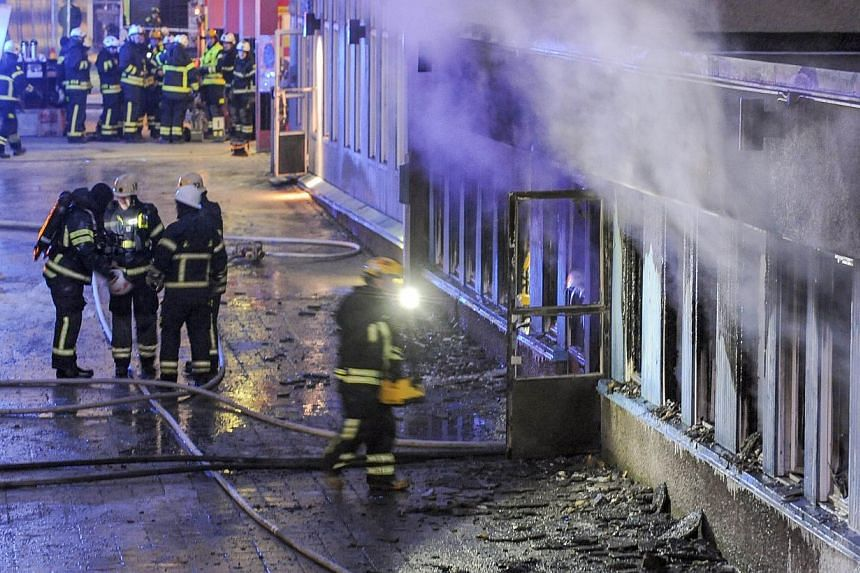 Smoke rises from the interior of a destroyed cellar mosque as firefighters search the remains of the building after an arson attack on Dec 25, 2014 in Eskilstuna, central Sweden. -- PHOTO: AFP