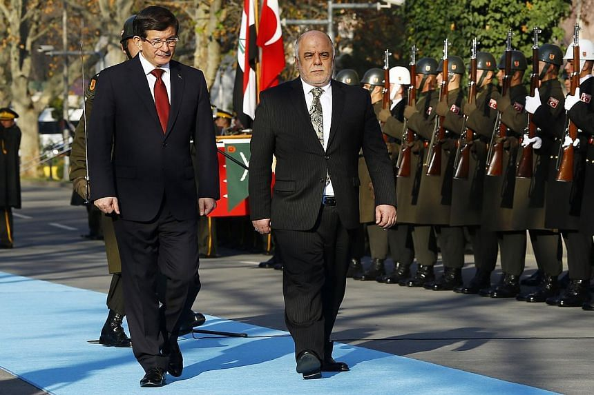 Turkey's Prime Minister Ahmet Davutoglu (left) and Iraqi Prime Minister Haider al-Abadi review a guard of honour during a welcoming ceremony in Ankara Dec 25, 2014. Iraq and Turkey on Thursday pledged to join forces to fight Islamic State insurgents