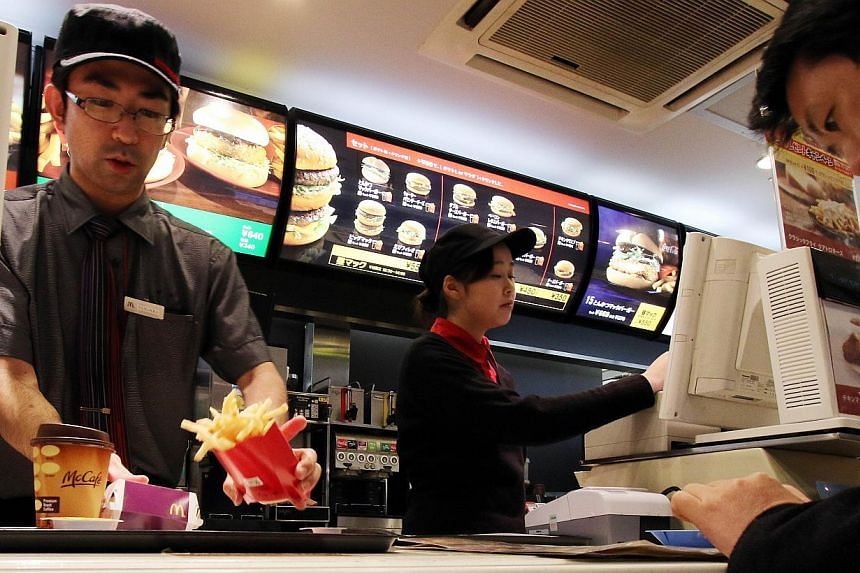 An employee serves french fries to a customer at a McDonald's restaurant in Tokyo on Dec 16, 2014. -- PHOTO: AFP