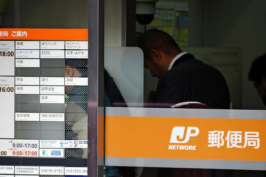 Customers use an ATM at a branch of Japan Post in the Ginza shopping district of central Tokyo on Dec26, 2014. -- PHOTO: AFP