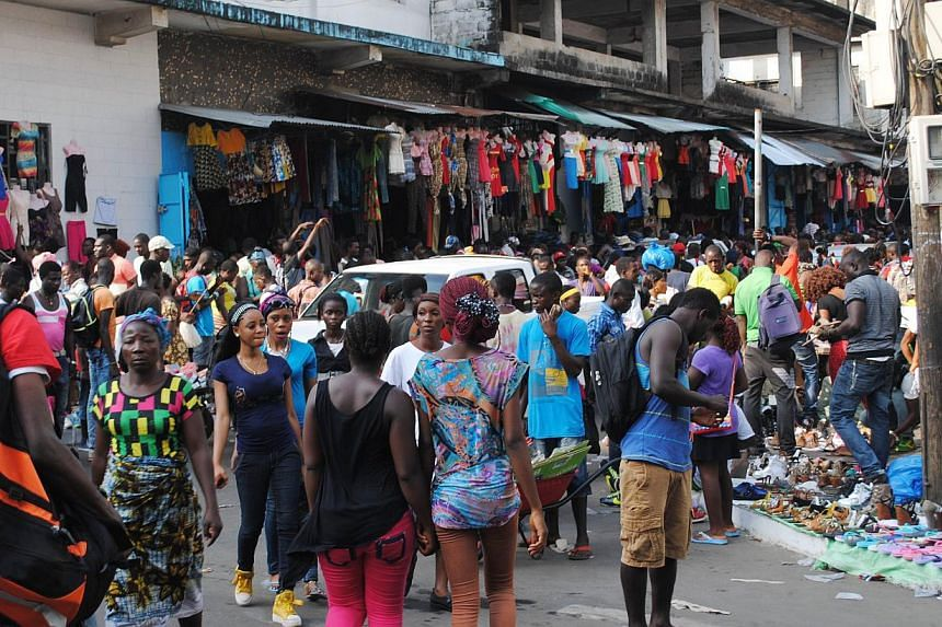 People walk in a market on Dec 24, 2014 in Monrovia.The Ebola epidemic has cast a dark shadow over Christmas this year in Liberia, where small businesses are especially feeling the pinch. -- PHOTO: AFP