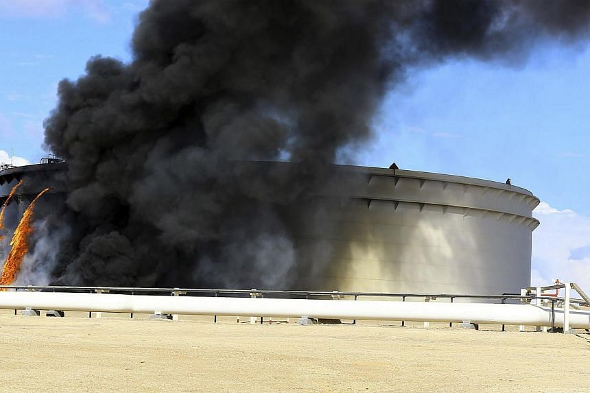 Black smoke billows from a storage oil tank in the port of Es Sider in Ras Lanuf Dec 25, 2014. Islamists killed at least 22 soldiers on Thursday after a surprise attack in which they used speedboats in a failed bid to seize some of Libya's main