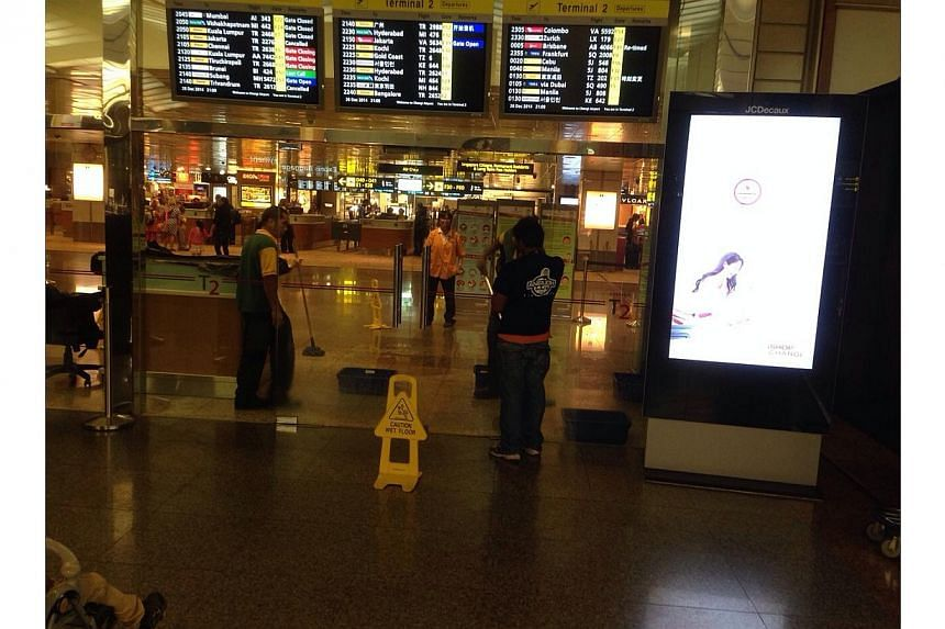 Workers mopping up the wet floor at Changi Airport Terminal Two. -- PHOTO: RONALD SNG