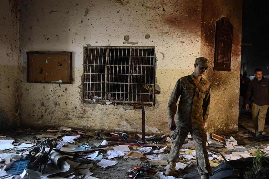 A Pakistani soldier walks amidst the debris in an army-run school a day after an attack by Talebanmilitants in Peshawar on Dec 17, 2014. -- PHOTO: AFP
