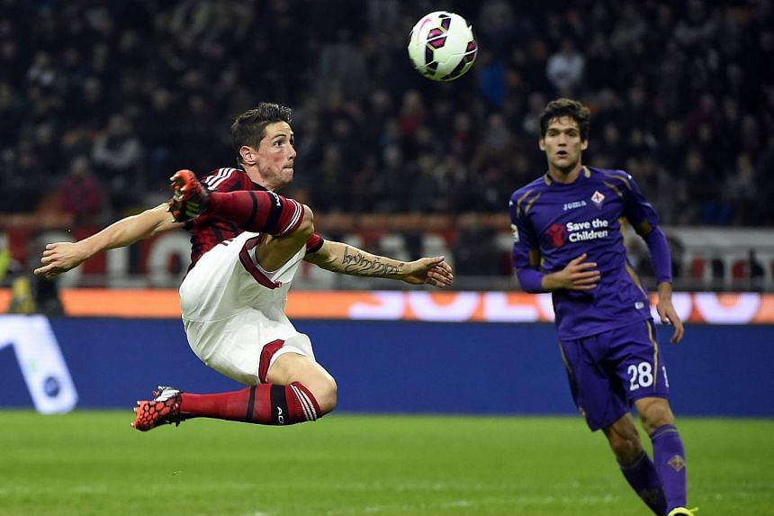 AC Milan's forward from Spain Fernando Torres (right) takes a shot during the Italian Serie A football match AC Milan vs Fiorentina on Oct 26, 2014 at the San Siro Stadium stadium in Milan. -- PHOTO: AFP