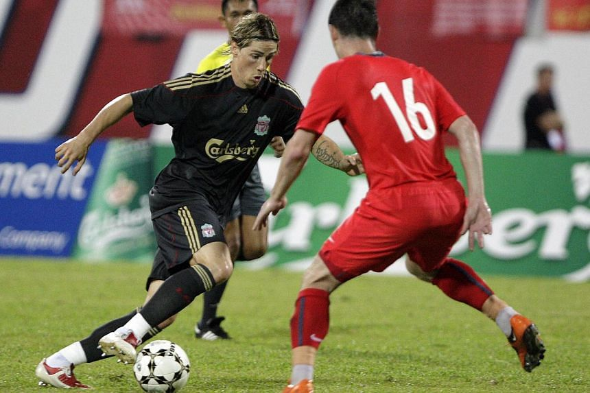 Liverpool's Spanish striker Fernando Torres (left) dribbles past an opponent during a friendly football match against Singapore's national team at the National Stadium on July 26, 2009, as part of Liverpool's Asian tour. -- PHOTO: ST FILE