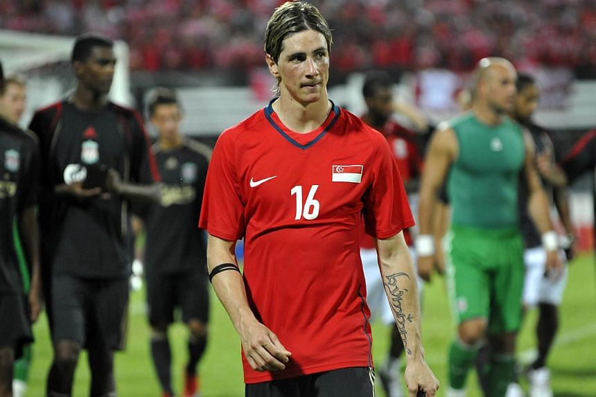 Liverpool's star striker Fernando Torres leaving the football pitch with his teammates, wearing Singapore defender Daniel Bennett's jersey, after the friendly match at the National Stadium on July 26, 2009.-- PHOTO: ST FILE