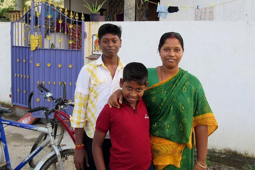 Madam Vijaylalitha with sons Ashwin (centre) and Abhi. Earlier this year, the family moved into this impressive two-storey home, which took more than $50,000 and ten years to build. -- PHOTO: ST FILE