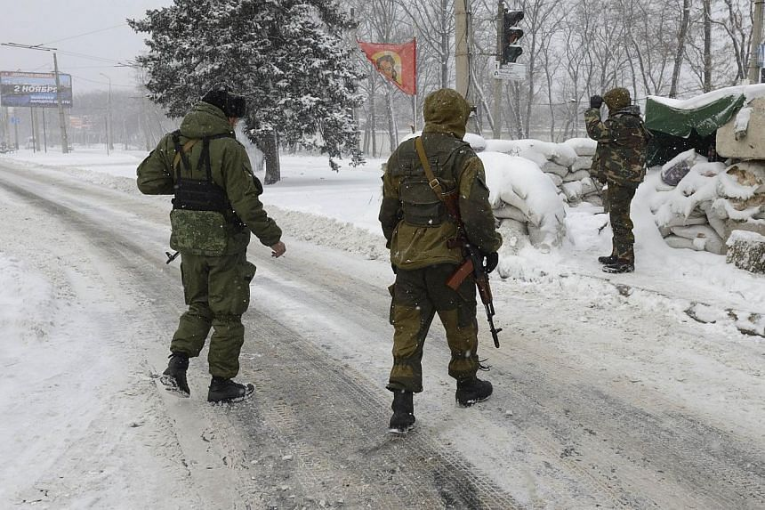 Pro-Russian rebels man a road on Nov 30, 2014 at the entrance of the eastern city of Donetsk controlled by pro-Russian rebels. -- PHOTO: AFP