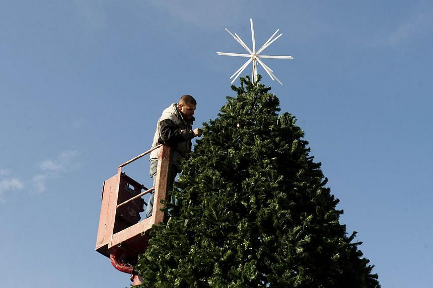 A municiple worker puts the final touches to a Christmas Tree in the main square in Pristina on Dec 20, 2014 ahead of Christmas and New Year celebrations in Kosovo. Kosovo authorities said Friday a potential car bombing was thwarted in Pristina on Ch