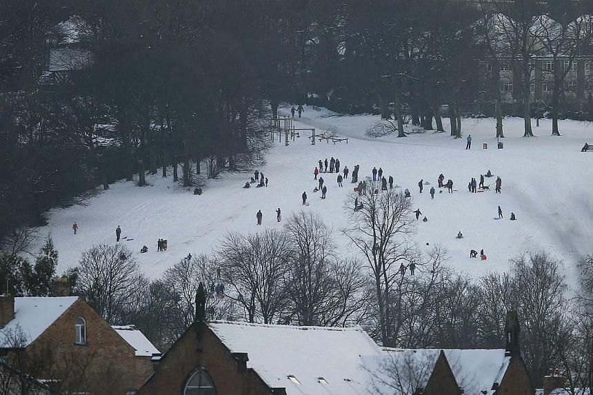 People sledge in a snow covered park in Sheffield, northern England on Dec 27, 2014. -- PHOTO:REUTERS
