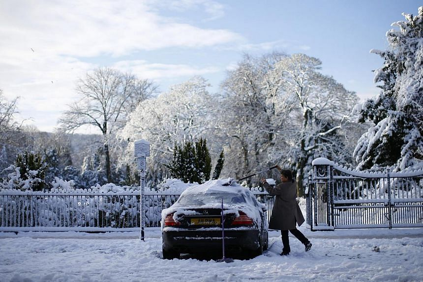 A man clears snow from his car in Buxton, central England on Dec 27, 2014. -- PHOTO: REUTERS