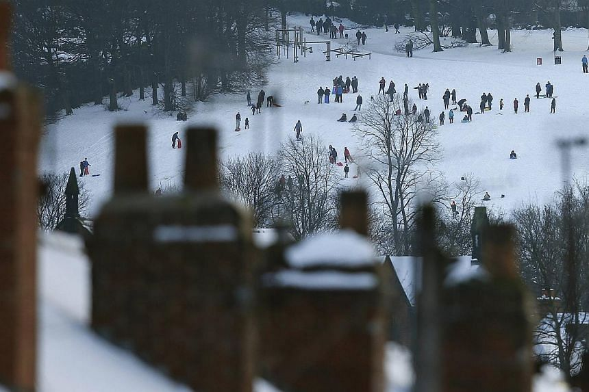 People sledge in a snow covered park in Sheffield, northern England on Dec 27, 2014. - PHOTO: REUTERS
