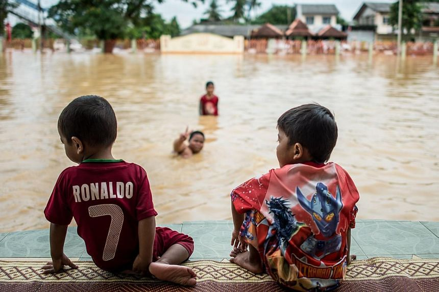 Two boys look on as their friends play in floodwaters in Pengkalan Chepa, near Kota Bharu on Dec 27, 2014.The number of people evacuated due to Malaysia's worst-ever floods jumped to more than 160,000 on Saturday, as Prime Minister Najib Razak