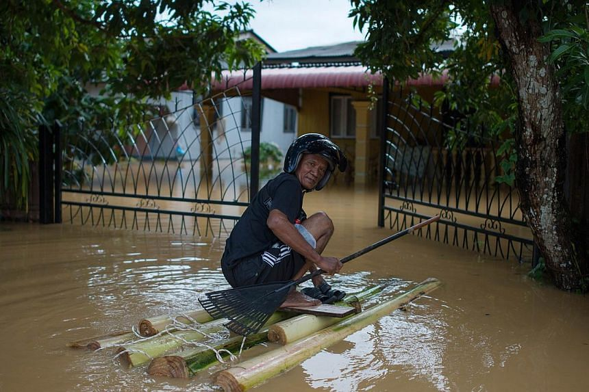 A man making his way to his house that has submerged in floodwaters in Pengkalan Chepa, near Kota Bharu, Kelantan, on Dec 27, 2014. Negeri Sembilan is the 8th Malaysian state affected by floods. -- PHOTO: AFP