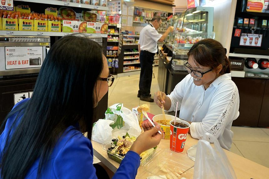 Administrative assistant Nuraihan Kasman (right), 29, with a friend having tom yam-flavoured cup noodles for lunch at a 7-Eleven store in Gopeng Street. Supermarkets and convenience stores said sales of convenience foods have risen by about 3 per cen